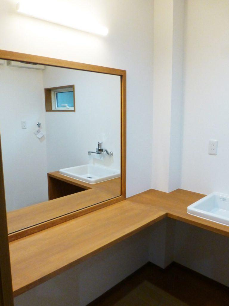 造作のカウンターに大きな鏡の洗面室